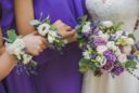 Close up of floral compositions worn around wrists of bridesmaids matching perfectly to bridal bouquet of flowers. Horizontal color photo of wedding event floristics.