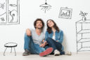 Portrait Of Happy Young Couple Sitting On Floor Looking Up While Dreaming Their New Home And Furnishing