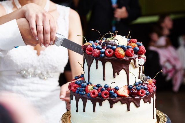 Cutting the wedding cake with berries on banquet