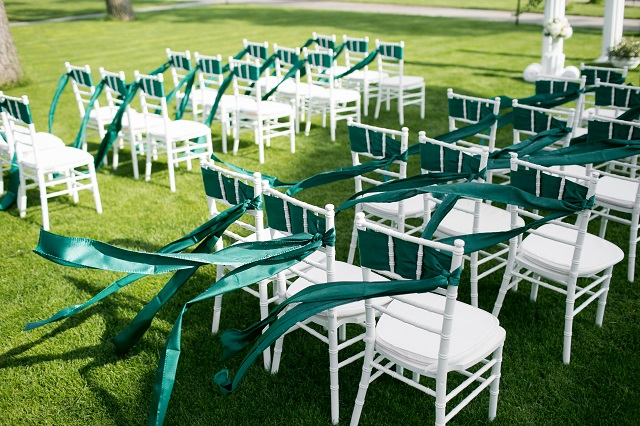 White wedding chairs with green ribbon outdoors