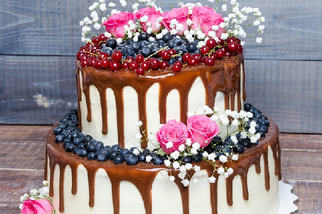 two layered color drip wedding cake with bilberries, red currants and roses