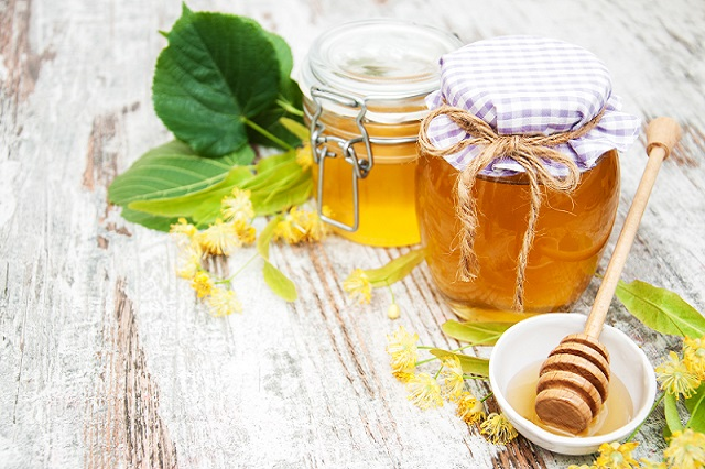 Jar with honey and linden flowers on a wooden background