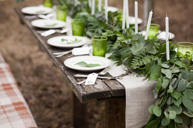 Weddind table setting with white plates and green glasses decorated with white candles, green leaves and eucalyptus and linen tablecloth outdoors