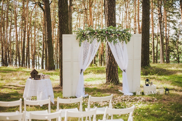 Beautiful outside white decor for wedding ceremony in scenic place in old wood. White arch decorated with fresh flowers and rows of many wooden chairs at high pine trees background.